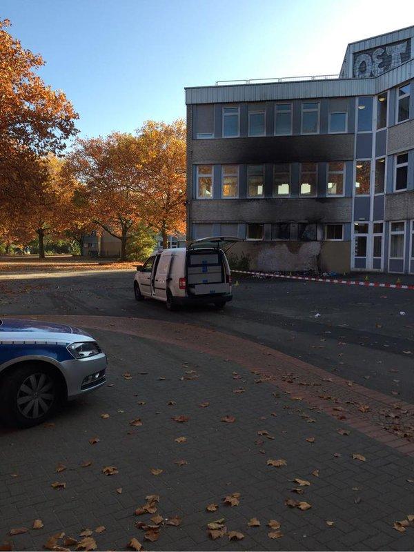 Verkohlte Hauswand einer Schule, davor Polizei-Absperrband