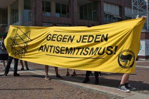 """Menschen stehen vor dem dortmunder Rathaus und halten ein Transparent mit der Aufschrift """"gegen jeden Antisemitismus"""""""