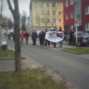 """Demonstrant:innen auf der Borsigstraße, vorneweg ein Transparent mit der Aufschrift """"Queers gegen Querdenken"""